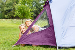 Two girls in camping tent. Two girls looking out of their camping tent royalty free stock photography