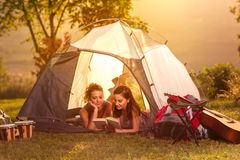 Two girls on camping trip. Two girls on camping trip lying in tent and reading book stock photography