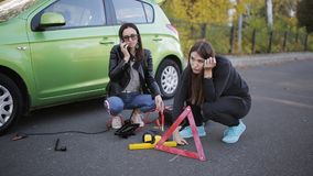 Two women call for help on the phone on the side of the road next to broken car. Two girls can`t have a car and are trying to understand the failure. Girls call stock video