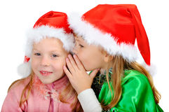Two girls in caps of Santy. On white stock image