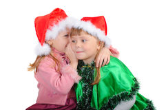 Two girls in caps of Santy. Are whispered among themselves over white stock image