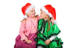 Two girls in caps of Santy. Over white background stock image