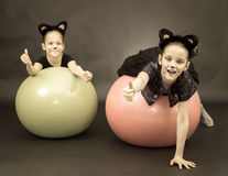 Two girls in cat costumes on fitness balls on black background i Royalty Free Stock Photography