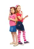 Two girls pretending to be big women. Two girls Caucasian and Asian playing to be big like mother brushing and making up face, isolated on white, full length Stock Photos
