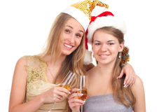 Two girls celebrate Christmas. With gifts and glasses in their hands studio shooting Royalty Free Stock Photo