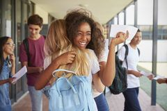 Two girls celebrating exam results in school corridor royalty free stock images
