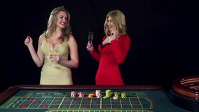 Two girls celebrating the victory in roulette. Black. Two cute girls drinking champagne and celebrating the victory in roulette, claps hand, beautiful high model stock video footage