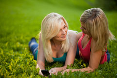 Two girls with a cell phone lying on the grass Stock Photography