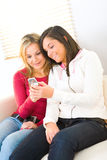 Two girls with cellphone. Two girls looking at cellphone and smiling. They're sitting on couch Stock Photo