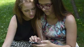 Two girls with cellphone in the park stock footage