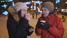 Two girls winter evening in the city drinking coffee and talking. Christmas evening walk two friends. stock footage