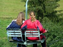 Two girls on a chair-lift in summer Royalty Free Stock Photography