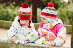 Two girls  with chalk Stock Images