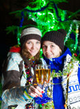 Two girls with champagne near Christmas tree Stock Image