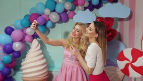 Two girls with champagne take a selfie at a party. Two lovely happy girls with glasses of champagne in their hands take a selfie in the room decorated with huge stock footage