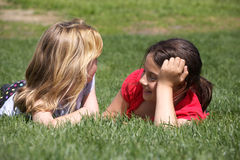 Two girls chatting in grass Royalty Free Stock Images