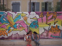 Two girls chatting in Marseille. Marseille, France - June 29, 2016: Two girls chatting in front of graffiti laden walls in Panier district of Marseille's old stock photography
