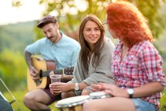 Two girls chatting in nature. Two girls chatting with music in green nature stock images
