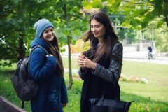 Two girls cheerfully spend time in the autumn park Stock Photos