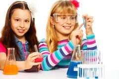 Two girls in chemistry class royalty free stock images