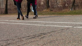 Two girls and a child are walking,walking feet on pavement. stock footage
