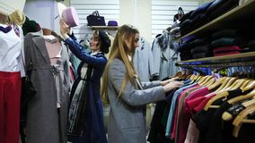 Two girls choose a clothes in a store. Girl stand near the mannequin take hat and dresses her on his friend stock video