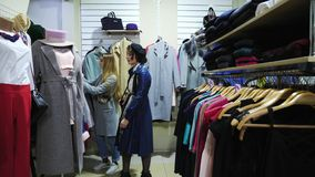 Two girls choose a coat in a store. Girl stand near the mannequin and take hat stock footage