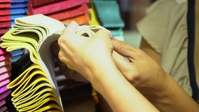 Two girls choose color of fabric from samples at the stand. Close up stock footage