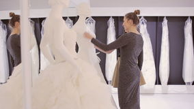 Two girls choose dress at bridal boutique. Two young woman chooses wedding gown at bridal store stock video