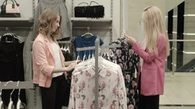 Two girls choose a dress. In mall stock video footage