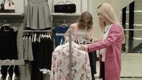 Two girls choose a dress. In mall stock video