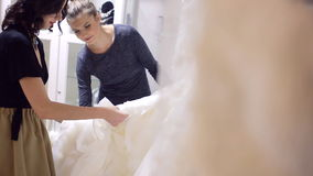 Two-girls choose dress. Two young woman chooses wedding gown at bridal store stock footage