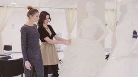 Two girls choose dress. Two young woman chooses wedding gown at bridal store stock video