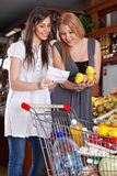 Two girls choose fruit Royalty Free Stock Image