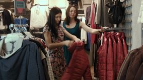 Two girls choose jackets stock video