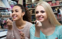 Two girls choose lip gloss Stock Images