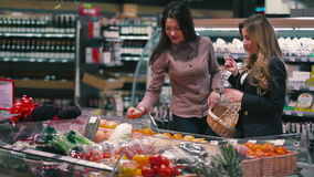 Two girls choosing the fruits in the supermarket. Two pretty girls standing near the fridge with fruits. The friends are choosing the fruits. Girls are talking stock video footage