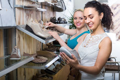 Two girls choosing shoes in the store Royalty Free Stock Photography