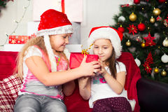 Two girls in Christmas costumes sitting on the Royalty Free Stock Photography