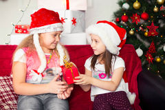 Two girls in Christmas costumes sitting on the Royalty Free Stock Photo