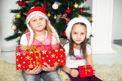 Two girls in Christmas costumes sitting under the Royalty Free Stock Image