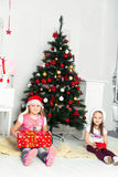 Two girls in Christmas costumes sitting under the Stock Image