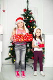 Two girls in Christmas costumes stand beside the Royalty Free Stock Images