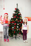 Two girls in Christmas costumes stand beside the Stock Photo