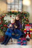 Two children in a Christmas decorated studio in pastel colors royalty free stock image