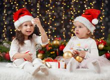 Two girls in christmas decoration with gift, dark background with illumination and boke lights, winter holiday concept Royalty Free Stock Photography