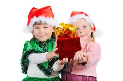 Two girls in the Christmas dress stretch a gift Stock Photo