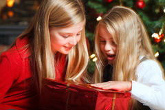 Two girls on christmas eve. Two girls in front of christmas tree and fire place opening a gift Stock Photos