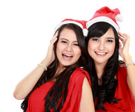 Two girls in christmas santa hat have fun. On white background Stock Images