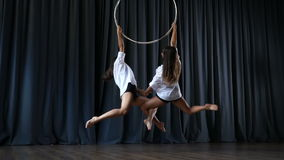 Two girls are circling on the aerial hoop and performs a gymnastic trick stock video footage